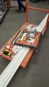 An orange Home Depot cart with pic pipes, moving blanket, zip ties, and more.