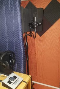 microphone, stand, audio interface, headphones, and a sound booth