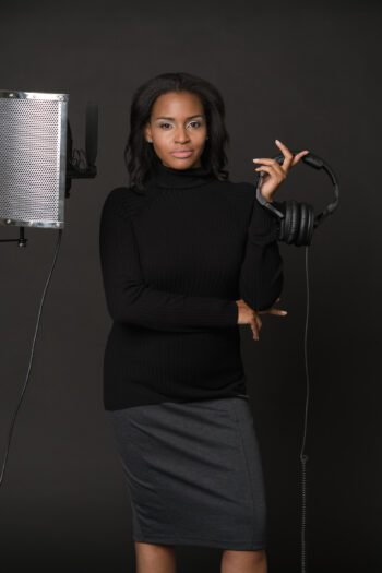 Michelle Francine Turner holding a set of headphone near a microphone and stand.
